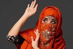 Πυροβολισμός στούντιο μιας νέας γοητευτικής γυναίκας που φορά την τερακότα hijab που διακοσμείται με τα τσέκια και το κόσμημα Αρα στοκ εικόνες με δικαίωμα ελεύθερης χρήσης