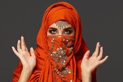 Πυροβολισμός στούντιο μιας νέας γοητευτικής γυναίκας που φορά την τερακότα hijab που διακοσμείται με τα τσέκια και το κόσμημα Αρα στοκ φωτογραφία με δικαίωμα ελεύθερης χρήσης