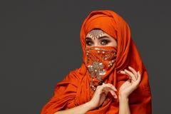Πυροβολισμός στούντιο μιας νέας γοητευτικής γυναίκας που φορά την τερακότα hijab που διακοσμείται με τα τσέκια και το κόσμημα Αρα στοκ εικόνες