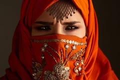 Πυροβολισμός στούντιο μιας νέας γοητευτικής γυναίκας που φορά την τερακότα hijab που διακοσμείται με τα τσέκια και το κόσμημα Αρα στοκ φωτογραφία