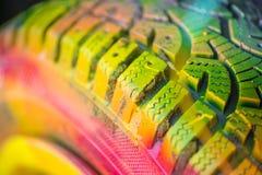 Πυροβολισμός της colorfully χρωματισμένης ρόδας αυτοκινήτων σε παλαιά, συντριφθε'ντα συντρίμμια αυτοκινήτων Στοκ φωτογραφίες με δικαίωμα ελεύθερης χρήσης