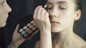 Πυροβολισμός του κυρίου που εφαρμόζει το ίδρυμα makeup φιλμ μικρού μήκους