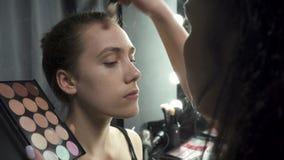 Πυροβολισμός του visagist που εφαρμόζει το ίδρυμα makeup απόθεμα βίντεο