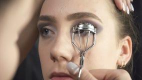 Πυροβολισμός του visagist που χρησιμοποιεί eyelash τις λαβίδες απόθεμα βίντεο