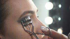Πυροβολισμός του visagist που χρησιμοποιεί eyelash το ρόλερ απόθεμα βίντεο