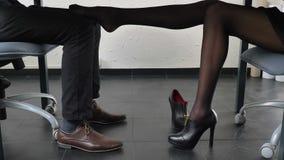 Πυροβολώντας στο πλαίσιο του πίνακα, το προκλητικό θηλυκό πόδι αγγίζει ήπια το πόδι ατόμων ` s, φλερτ, έννοια 50 παρενόχλησης fps φιλμ μικρού μήκους