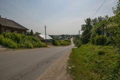 Πυροβοληθείς του του χωριού δρόμου και μερικών εξοχικών σπιτιών το καλοκαίρι Στοκ Φωτογραφίες