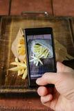 Πυροβοληθείσα Smartphone φωτογραφία τροφίμων - τηγανιτές πατάτες με το αλάτι Στοκ Φωτογραφία