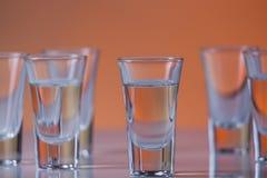Πυροβοληθε'ν γυαλί που γεμίζουν με τη βότκα σε ένα πορτοκαλί υπόβαθρο Στοκ Εικόνες