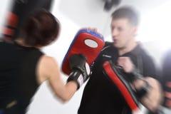 Πυροβοληθε'ν δράση punching τα μαξιλάρια στοκ φωτογραφίες