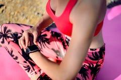 Πυροβολισμός κινηματογραφήσεων σε πρώτο πλάνο Θηλυκός αθλητής που χρησιμοποιεί την ικανότητα app στο έξυπνο ρολόι της που ελέγχει Στοκ Εικόνες