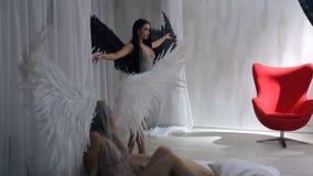 Πυροβολισμός στούντιο δύο προτύπων ξανθών και των αγγέλων brunette με τα φτερά απόθεμα βίντεο