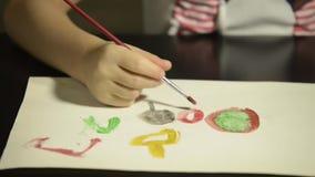 Πυροβόλησε την κινηματογράφηση σε πρώτο πλάνο του χεριού ενός παιδιού με μια ζωγραφική βουρτσών με το watercolor σε χαρτί απόθεμα βίντεο
