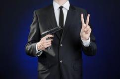 Πυροβόλα και θέμα ασφάλειας: ένα άτομο σε ένα μαύρο κοστούμι που κρατά ένα πυροβόλο όπλο σε ένα σκούρο μπλε υπόβαθρο στο στούντιο Στοκ Εικόνες