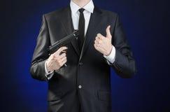 Πυροβόλα και θέμα ασφάλειας: ένα άτομο σε ένα μαύρο κοστούμι που κρατά ένα πυροβόλο όπλο σε ένα σκούρο μπλε υπόβαθρο στο στούντιο Στοκ φωτογραφία με δικαίωμα ελεύθερης χρήσης