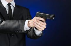 Πυροβόλα και θέμα ασφάλειας: ένα άτομο σε ένα μαύρο κοστούμι που κρατά ένα πυροβόλο όπλο σε ένα σκούρο μπλε υπόβαθρο στο στούντιο Στοκ Φωτογραφία