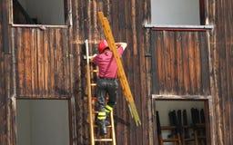 Πυροσβέστες κατά τη διάρκεια μιας επίδειξης της χρησιμοποίησης της σκάλας για να φθάσει στοκ εικόνες