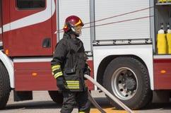 Πυροσβέστες με τη μάνικα για να σβήσει τις πυρκαγιές Στοκ Εικόνες