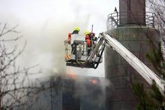Πυροσβέστες που εξαφανίζουν την πυρκαγιά στην υδραυλική πλατφόρμα γερανών στοκ φωτογραφίες