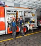 Πυροσβέστες που κλίνουν στο φορτηγό στο πυροσβεστικό σταθμό Στοκ φωτογραφίες με δικαίωμα ελεύθερης χρήσης