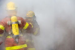 2 πυροσβέστες σε λειτουργία περιβάλλουν με τον καπνό Στοκ Φωτογραφία