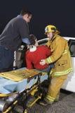Πυροσβέστης και γιατρός που παίρνουν έξω το θύμα από το αυτοκίνητο Στοκ εικόνα με δικαίωμα ελεύθερης χρήσης