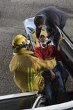 Πυροσβέστης και γιατρός που παίρνουν έξω το θύμα από το αυτοκίνητο Στοκ Εικόνες