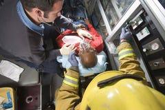 Πυροσβέστης και γιατρός που φροντίζουν το ανώτερο άτομο Στοκ Φωτογραφίες