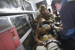 Πυροσβέστης και γιατρός EMT που βοηθούν μια τραυματισμένη γυναίκα Στοκ Εικόνες