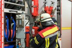 Πυροσβέστης με έναν πυροσβεστήρα στο πυροσβεστικό όχημα Στοκ Φωτογραφία