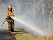 Πυροσβέστης με μια μάνικα σε μια πυρκαγιά θάμνων σε μια προαστιακή περιοχή της πόλης Knox στην ανατολή της Μελβούρνης Στοκ εικόνες με δικαίωμα ελεύθερης χρήσης