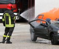 Πυροσβέστης με το κράνος από το αυτοκίνητο που καίγεται με τον αφρό Στοκ Εικόνα