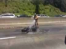 Πυροσβέστης που εξαφανίζει την απανθρακωμένη μοτοσικλέτα στην εθνική οδό στοκ εικόνες
