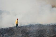 Πυροσβέστης που διασχίζει την απανθρακωμένη έκταση Στοκ Φωτογραφίες