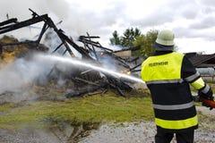 Πυροσβέστης στη δράση στο κάψιμο του σπιτιού Στοκ Εικόνα
