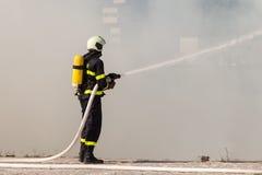 Πυροσβέστης στις προστατευτικές εργασίες κοστουμιών με τη μάνικα νερού Πάλη για μια επίθεση πυρκαγιάς Στοκ εικόνες με δικαίωμα ελεύθερης χρήσης