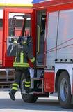 Πυροσβέστης στο άλμα δράσης κάτω γρήγορα από το πυροσβεστικό όχημα Στοκ Εικόνες