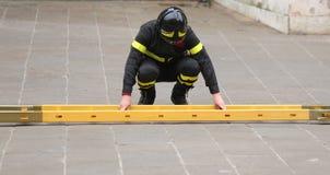 Πυροσβέστης συγκεντρώνοντας τη σκάλα κατά τη διάρκεια μιας έκτακτης ανάγκης Στοκ Εικόνες