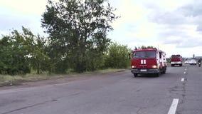 Πυροσβεστικά οχήματα στη δράση με τους ανοιγμένους ηλεκτρικούς φακούς σκηνή Οδήγηση οχημάτων μηχανών προσβολής του πυρός στην πυρ απόθεμα βίντεο