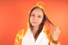 Πυτζάμες υπό μορφή giraffe συναισθηματικό πορτρέτο ενός κοριτσιού σε ένα πορτοκαλί υπόβαθρο τρελλή και αστεία γυναίκα σε ένα κοστ στοκ εικόνες