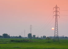 Πυλώνας μετάδοσης ηλεκτρικής ενέργειας στον τομέα στο ηλιοβασίλεμα Στοκ εικόνα με δικαίωμα ελεύθερης χρήσης