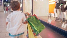 Πωλήσεις αγορών, αγόρι παιδιών με τις τσάντες στα τρεξίματα χεριών μέσω της λεωφόρου μετά από τις αγορές στις μπουτίκ μόδας απόθεμα βίντεο