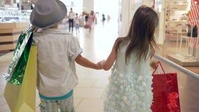 Πωλήσεις αγορών, λίγος αδελφός με την αδελφή με τα μέρη των συσκευασιών που περπατά μαζί να κρατήσει τα χέρια στη λεωφόρο μετά απ απόθεμα βίντεο