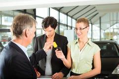 Πωλήσεις αυτοκινήτων - έμπορος που δίνει στη γυναίκα το αυτόματο πλήκτρο Στοκ Εικόνες