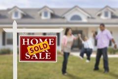 Πωλημένο σημάδι ακίνητων περιουσιών και ισπανική οικογένεια στο σπίτι Στοκ Εικόνα