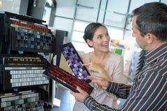 Πωλητής ανδρών που βοηθά τον πελάτη γυναικών για να επιλέξει την επικεράμωση με τη δειγματοληπτική συσκευή στοκ εικόνες