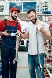 Πωλητής και γενειοφόρος τοποθέτηση πελατών με τα γιγαντιαία γαλλικά κλειδιά στο κατάστημα εργαλείων δύναμης Στοκ Φωτογραφίες