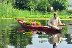 Πωλητής λουλουδιών σε ένα shikara στο Σπίναγκαρ, Κασμίρ, Ινδία στοκ εικόνα