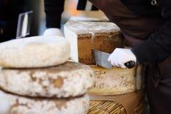 Πωλητής που κόβει το οργανικό τυρί στην αγορά αγροτών στο Στρασβούργο, Γαλλία Στοκ Εικόνες