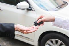 Πωλητής που προσφέρει το κλειδί αυτοκινήτων σε έναν επιχειρηματία από τον έμπορο αυτοκινήτων Στοκ φωτογραφία με δικαίωμα ελεύθερης χρήσης